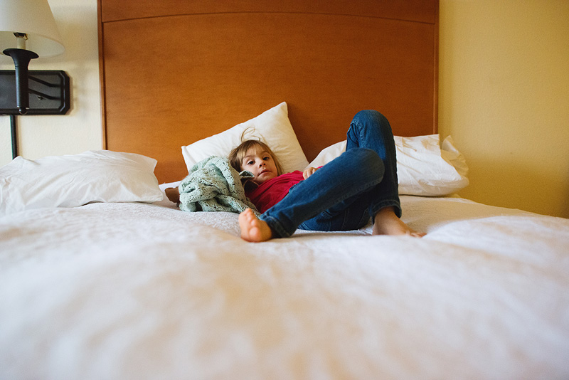 Girl laying in a hotel bed.