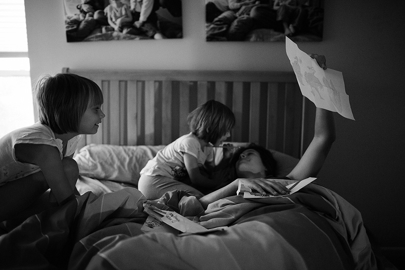 Kids snuggling their mom in bed.