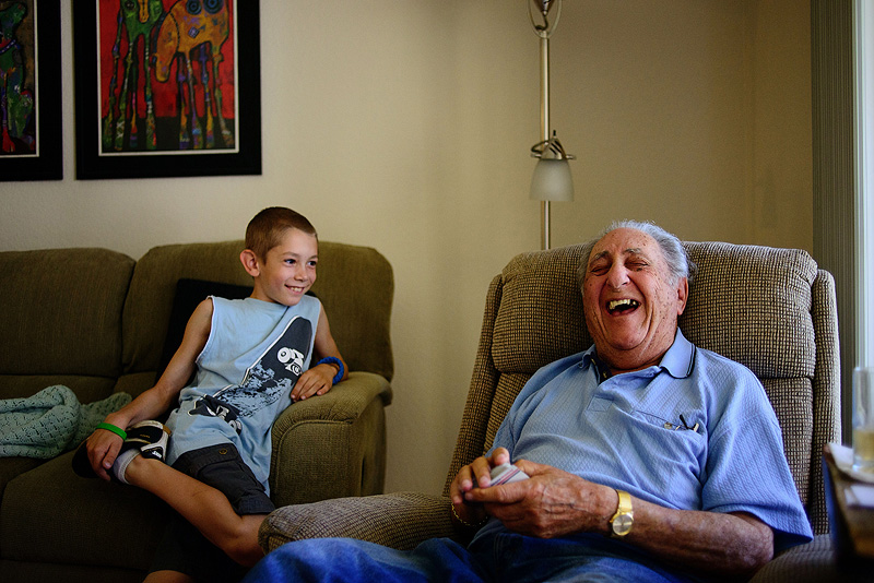 Grandpa laughing with his great grandson.