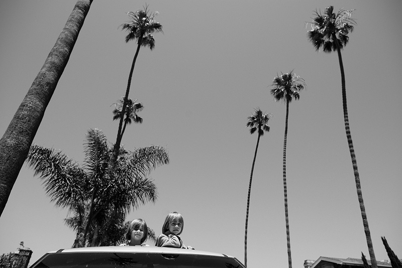 Girls sticking their heads out of the sun roof.
