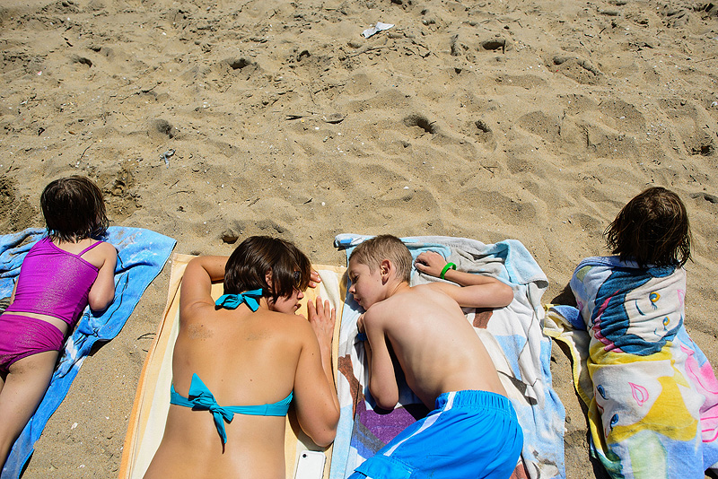 Family laying on the beach in the sun.