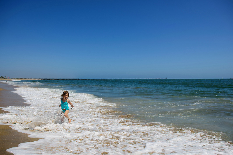 Girl playing in Seal Beach water.