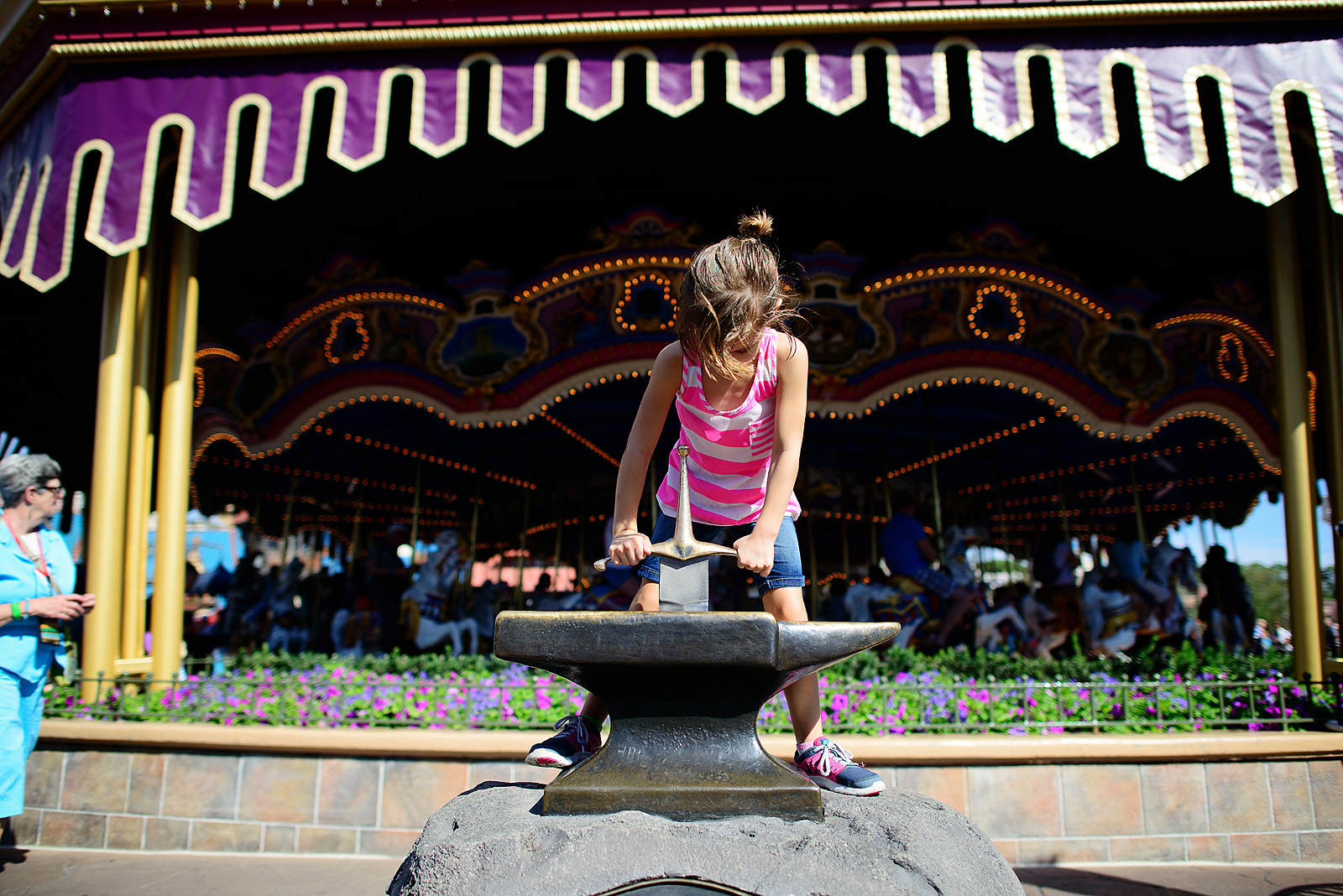 girl trying to pull the sword out of the stone at Magic Kingdom