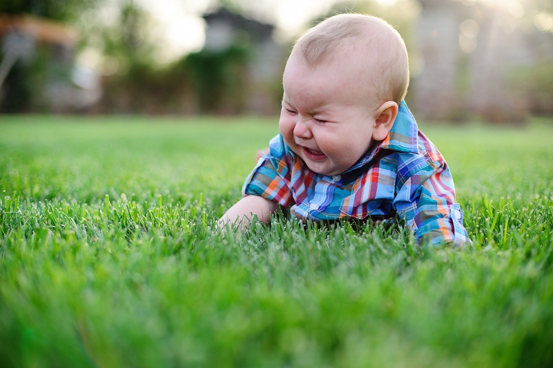 Cute picture of a baby crying in the grass.