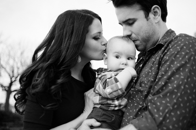 Parents kissing their baby boy.