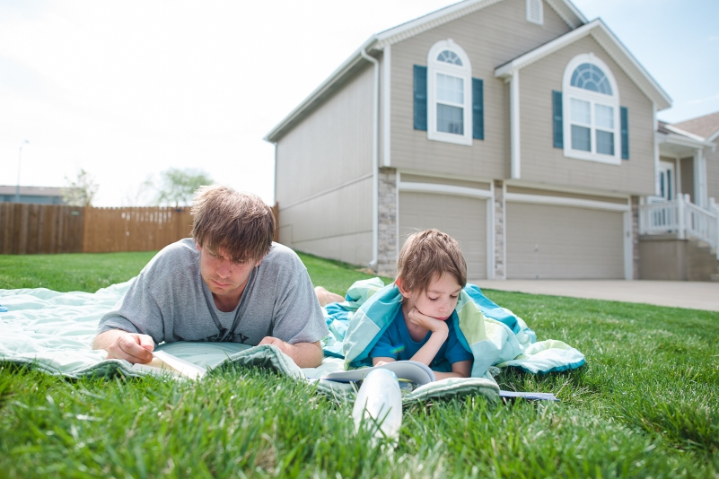 father and son reading in the grass.